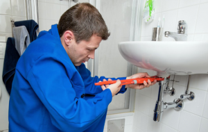a plumber tightens a loose sink drain with a pipe wrench